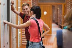 Students leaning against locker flirting Stock Photos