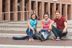Smiling students sitting on stairs holding tablet - stock photo