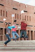 Happy students jumping in the air holding exam - stock photo