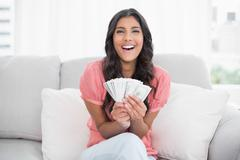Gleeful cute brunette sitting on couch holding money - stock photo