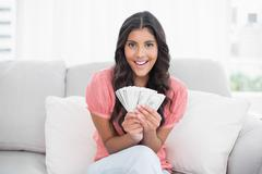 Cheerful cute brunette sitting on couch holding money Stock Photos