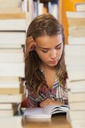 Focused pretty student studying between piles of books - stock photo