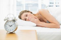 Attractive tired woman lying in her bed under the cover - stock photo