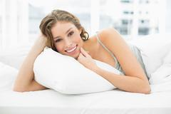 Peaceful content woman lying in her bed under the cover Stock Photos