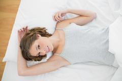 Attractive slender woman lying under the cover on her bed - stock photo