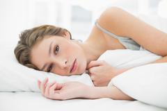 Peaceful young woman relaxing under the cover on her bed - stock photo