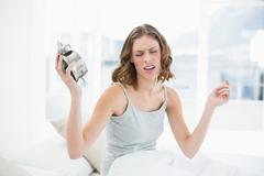 Upset young woman holding an alarm clock sitting on her bed - stock photo
