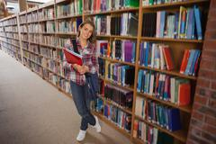 Pretty smiling student holding notebooks - stock photo