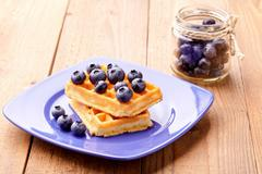 Hand made wafers on a dark blue plate and berries a blueberry in a glass jar Stock Photos