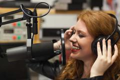 Cheerful beautiful singer recording a song - stock photo