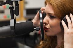 Focused beautiful singer recording a song - stock photo