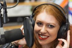 Smiling beautiful singer recording a song - stock photo