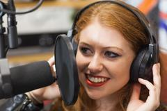 Happy beautiful singer recording a song - stock photo