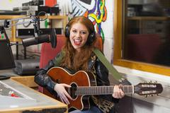 Smiling beautiful singer recording and playing guitar - stock photo