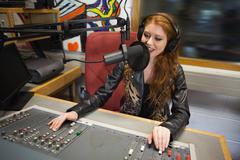Happy beautiful radio host moderating - stock photo