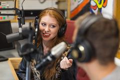 Attractive happy radio host interviewing a guest Stock Photos
