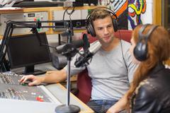 Attractive content radio host interviewing a guest Stock Photos