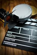 clapper board with movie light and film reels - stock photo