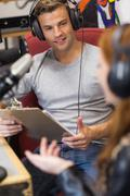 Attractive radio host interviewing a guest holding clipboard Stock Photos