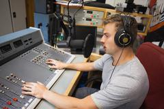 Handsome focused radio host moderating Stock Photos