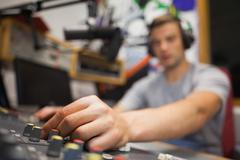 Handsome radio host moderating touching switch - stock photo