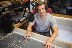 Handsome cheerful radio host moderating - stock photo