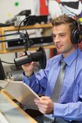 Well dressed happy radio host moderating - stock photo