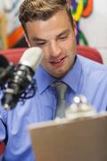 Well dressed smiling radio host moderating holding clipboard - stock photo
