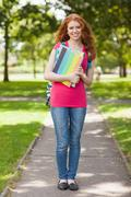Gorgeous smiling student carrying notebooks - stock photo