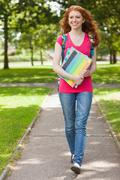 Gorgeous smiling student walking and carrying notebooks - stock photo