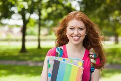Gorgeous smiling student holding notebooks - stock photo