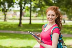 Stock Photo of Gorgeous smiling student using tablet