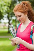 Gorgeous happy student holding notebooks texting - stock photo
