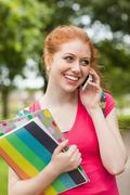 Gorgeous cheerful student holding notebooks phoning - stock photo