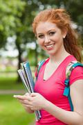 Gorgeous cheerful student holding notebooks texting - stock photo