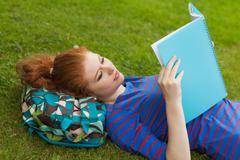 Stock Photo of Gorgeous focused student lying on grass reading notes