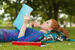 Gorgeous serious student lying on grass reading notes - stock photo