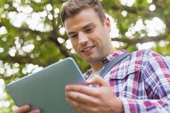 Stock Photo of Handsome happy student using tablet