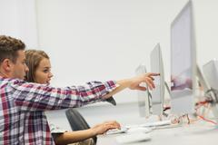 Kaksi opiskelijaa työskentelee tietokoneella osoittamalla sitä Kuvituskuvat