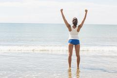 Lovely slim woman standing on beach raising her arms - stock photo