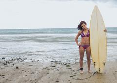 Full length of a bikini woman holding surfboard at beach - stock photo