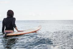 Stock Photo of Rear view of a woman with surfboard in the water