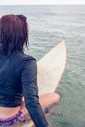 Stock Photo of Rear view of a woman sitting on surfboard in water