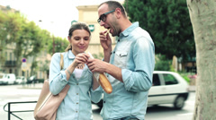 Attractive couple eating baguette standing by city street HD Stock Footage