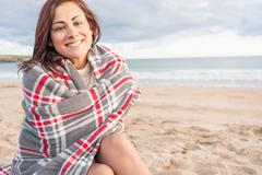 Portrait of a woman covered with blanket at beach - stock photo