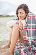 Woman covered with blanket at beach - stock photo