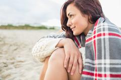 Stock Photo of Side view of woman covered with blanket at beach