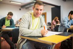 Smiling student with others writing notes in classroom - stock photo