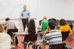 Attentive students with teacher in the classroom - stock photo