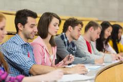 Students writing notes in a row at the lecture hall Stock Photos
